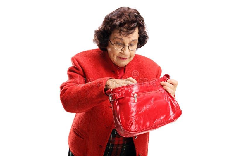 Señora mayor que busca a través de su bolso imagen de archivo libre de regalías