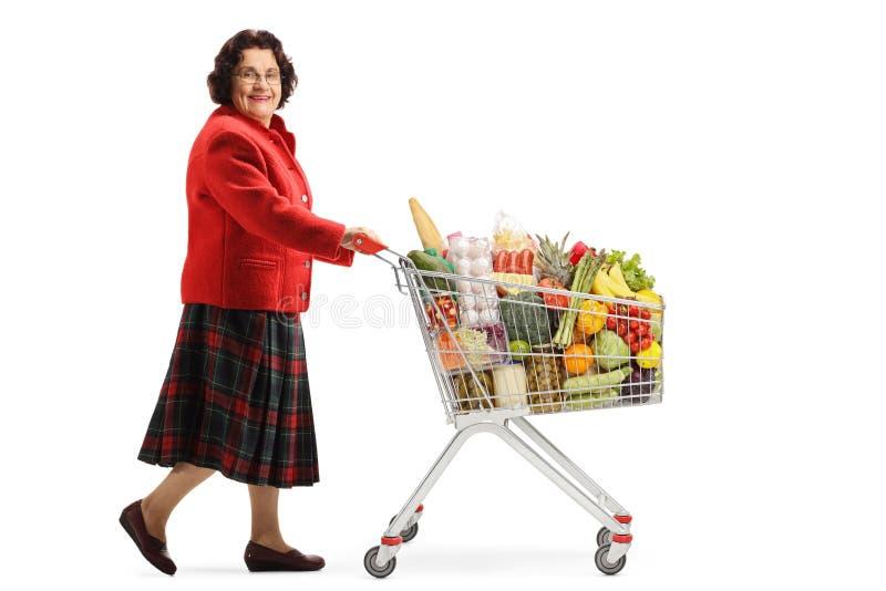 Señora mayor que camina con un carro de la compra con la comida y que sonríe en la cámara fotos de archivo libres de regalías