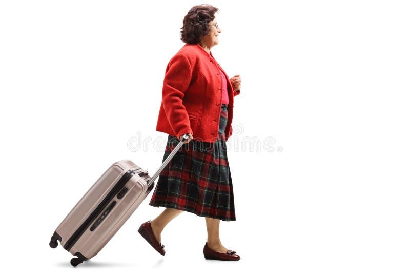 Señora mayor que camina y que tira de una maleta foto de archivo libre de regalías