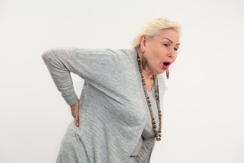 Señora mayor que hace el dolor de espalda aislar fotografía de archivo libre de regalías