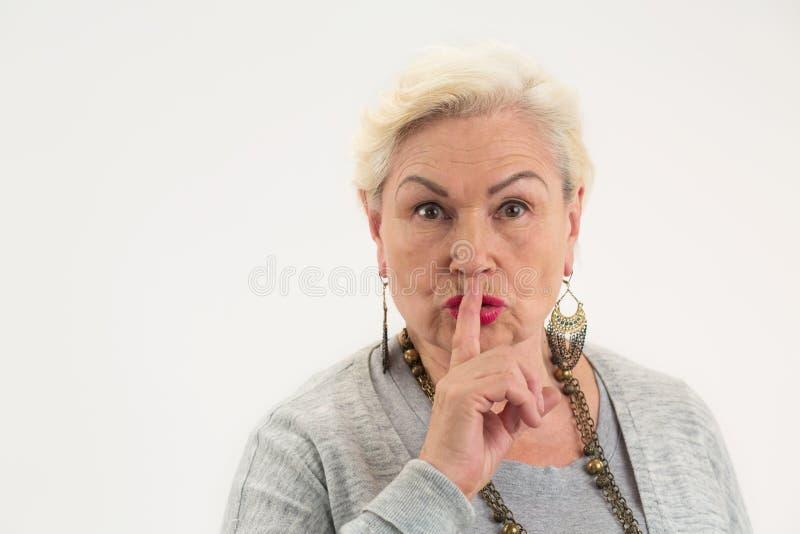 Señora mayor que muestra gesto del silencio fotografía de archivo