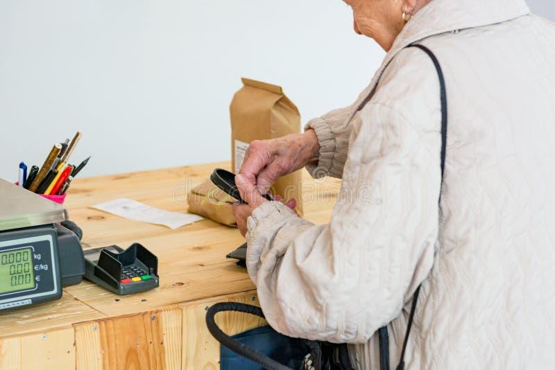 Señora mayor que paga algunos productos orgánicos en el contador de la tienda imagen de archivo
