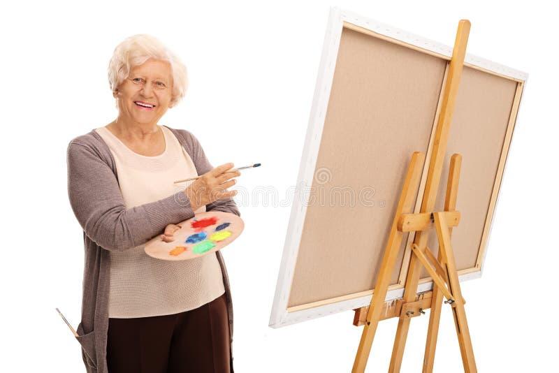 Señora mayor que presenta al lado de una lona fotografía de archivo libre de regalías