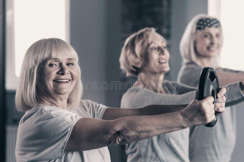 Señora mayor que se resuelve con el disco del peso con los amigos fotos de archivo libres de regalías
