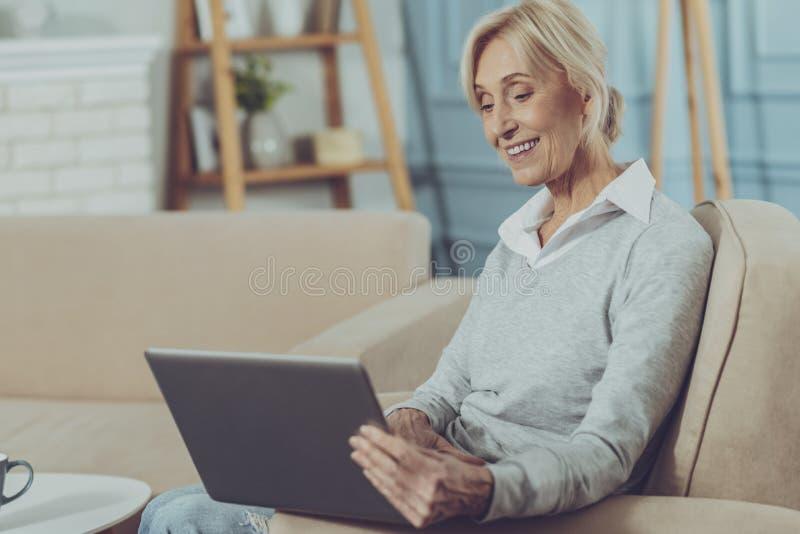 Señora mayor que se sienta con el ordenador portátil imágenes de archivo libres de regalías