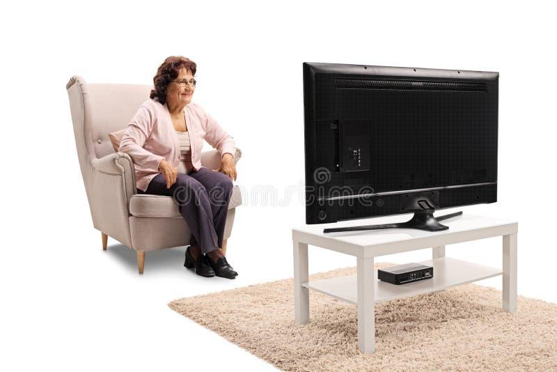 Señora mayor que se sienta en una butaca y una televisión de observación fotos de archivo libres de regalías