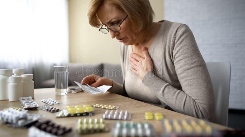 Señora mayor que siente calidad mal, mal de la automedicación peligrosa de la medicación fotografía de archivo