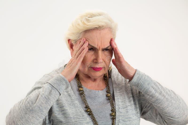 Señora mayor que tiene dolor de cabeza foto de archivo libre de regalías