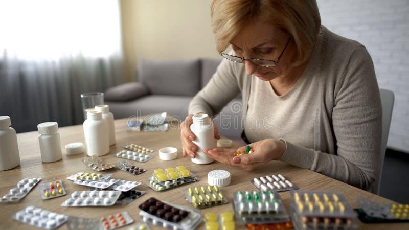 Señora mayor que toma a demasiado las píldoras, sintiendo mal, automedicación del problema del corazón foto de archivo libre de regalías