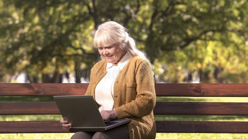 Señora mayor que trabaja en el ordenador portátil al aire libre en el parque, tecnología de la información foto de archivo libre de regalías
