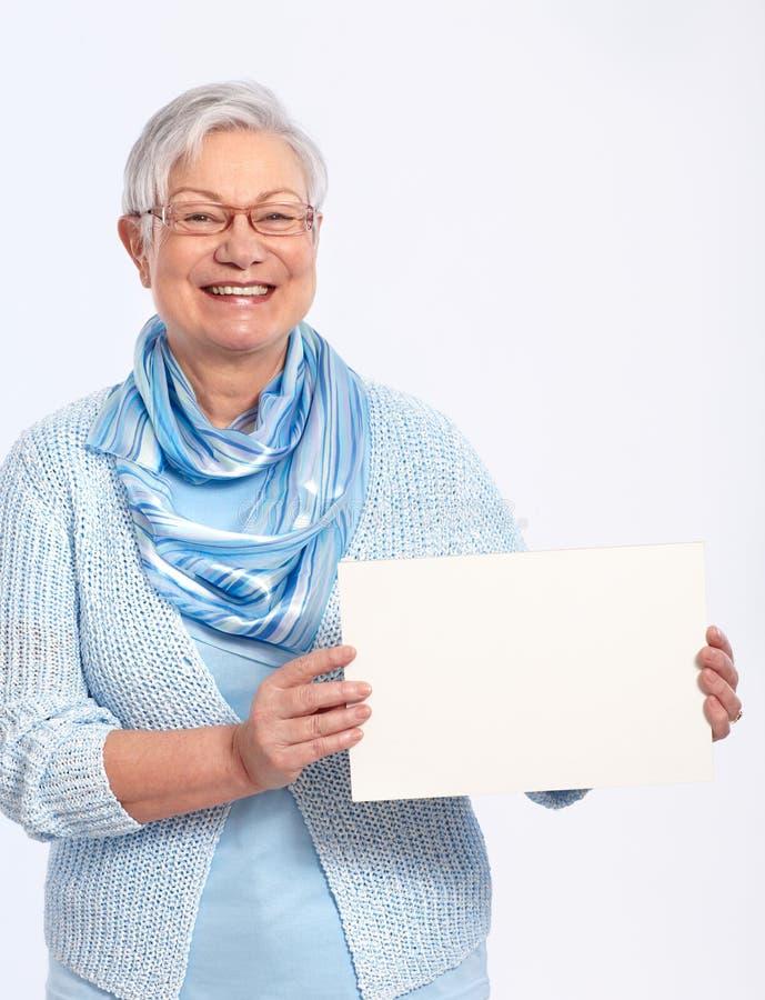 Señora mayor sonriente con la hoja en blanco foto de archivo libre de regalías