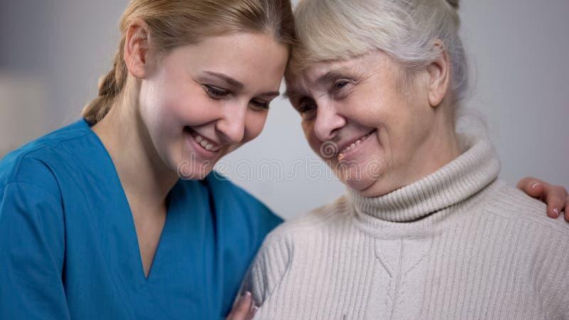 Señora mayor sonriente de abrazo y favorable del trabajador médico en clínica de reposo fotos de archivo libres de regalías