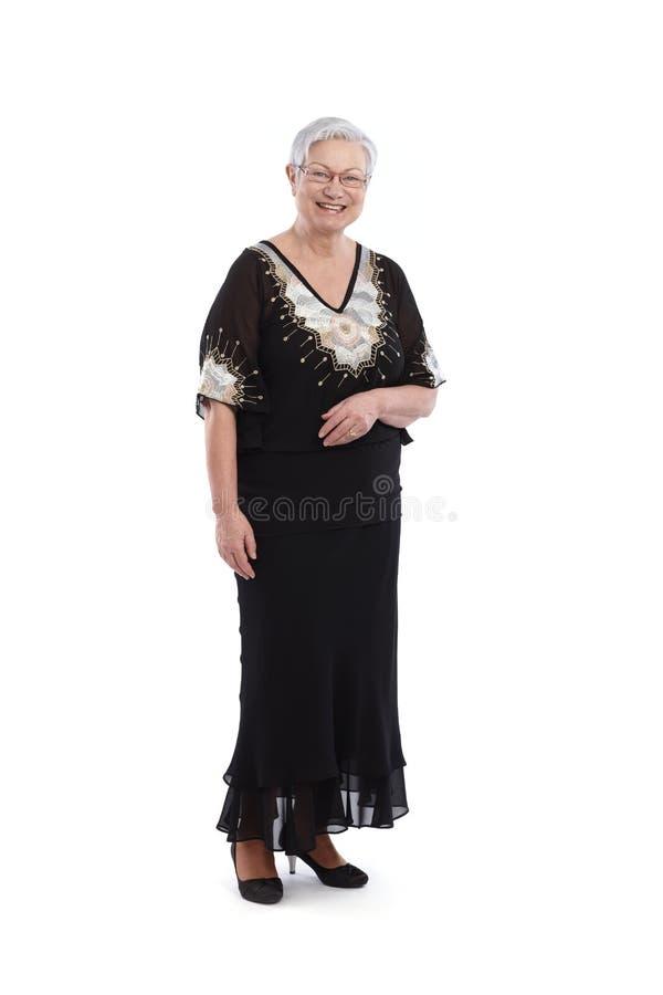 Señora mayor sonriente en vestido de noche imagen de archivo