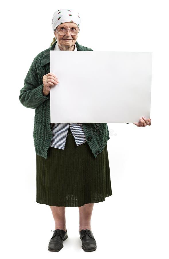 Señora mayor sonriente que sostiene la hoja en blanco en manos imágenes de archivo libres de regalías