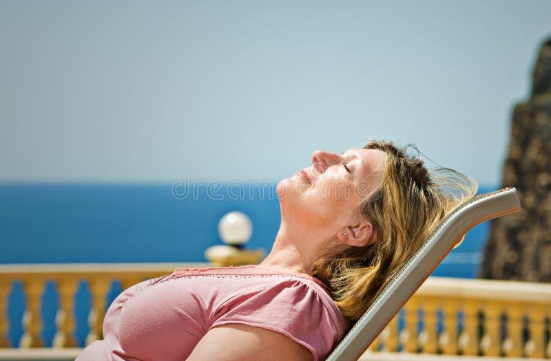 Señora mayor Sunbathing contra el contexto costero fotos de archivo libres de regalías