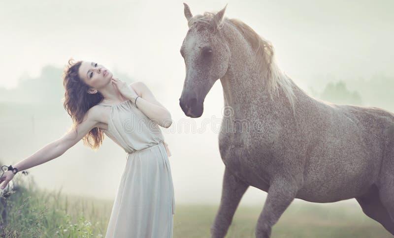 Señora morena atractiva y caballo manchado fotos de archivo
