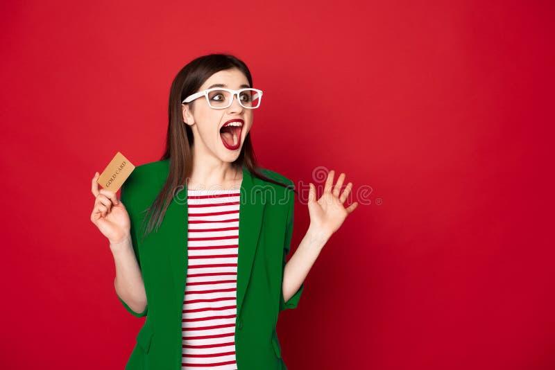 Se?ora morena sorprendida feliz con la tarjeta de cr?dito imagen de archivo