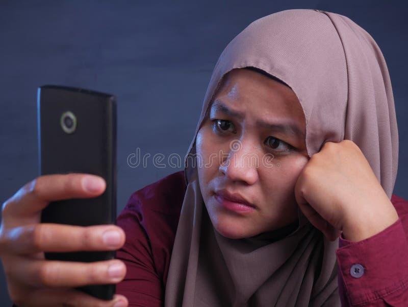 Señora musulmán Talking Texting en el teléfono, expresión enojada de Disapponted del trastorno imagenes de archivo