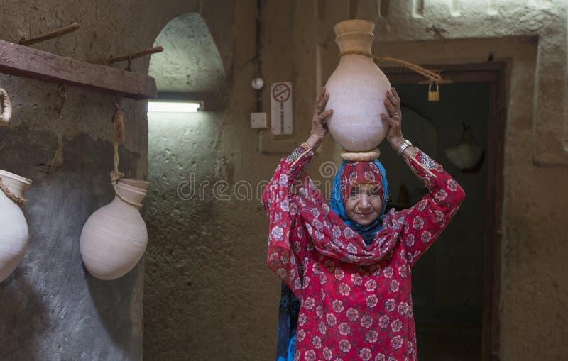 Señora omaní en el equipo del iraditional que pone un tarro del agua en su cabeza fotografía de archivo