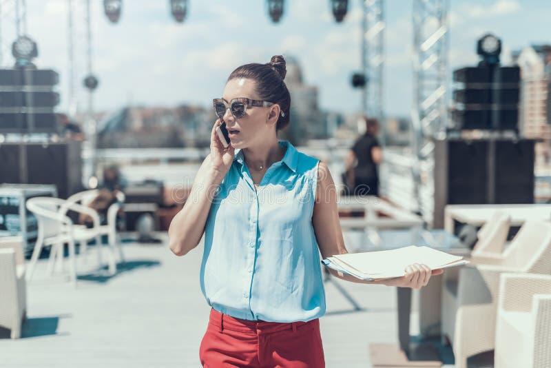Señora ordenada que dice en el teléfono contemporáneo al aire libre foto de archivo