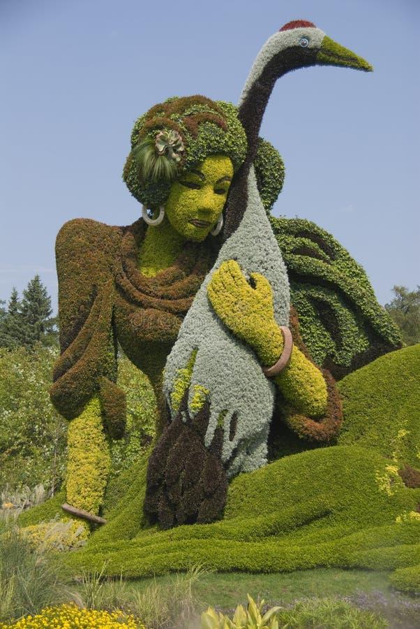 Señora oriental con la cigüeña, escultura botánica. foto de archivo libre de regalías