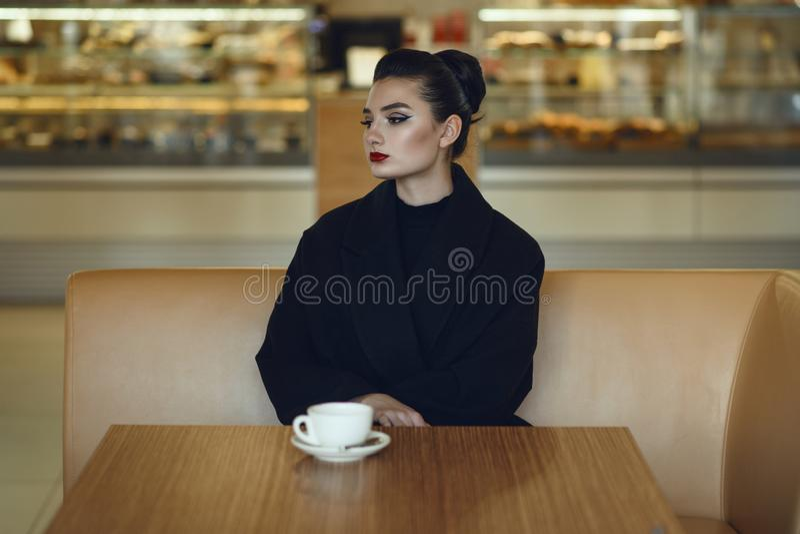 Señora pensativa hermosa que se sienta solamente en el café de consumición del café agradable imágenes de archivo libres de regalías