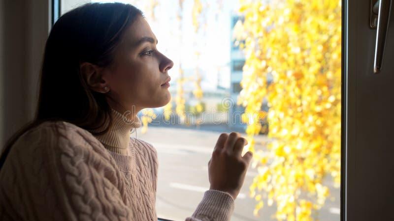 Señora pensativa que mira a través de la ventana, experimentando el desempleo de las dificultades de la vida fotos de archivo