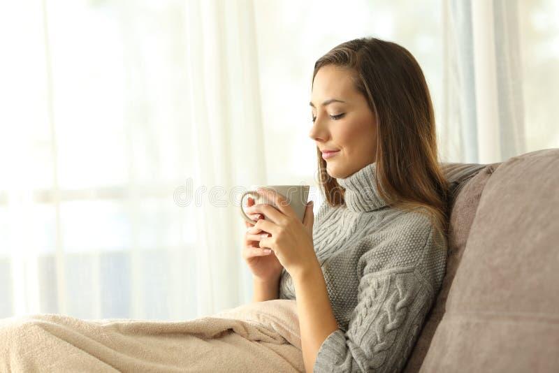 Señora pensativa que sostiene una taza de café en casa en invierno imagen de archivo