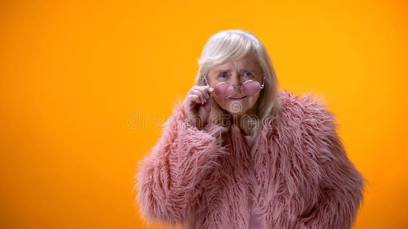 Señora positiva de envejecimiento que saca los vidrios, mirando directamente la cámara, escudriñando fotos de archivo