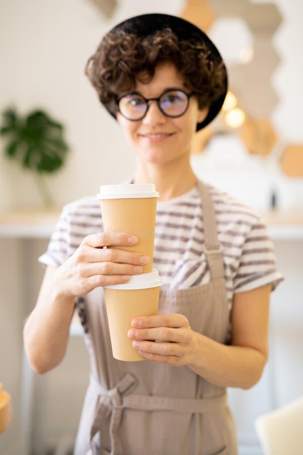 Señora positiva en delantal que prepara el café sabroso en café foto de archivo