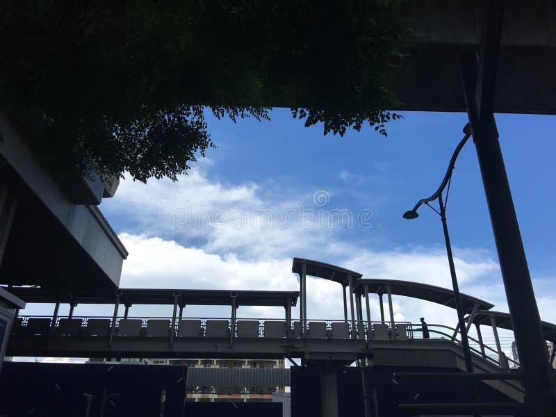 Señora que camina en la escalera móvil de la estación del skytrain fotos de archivo