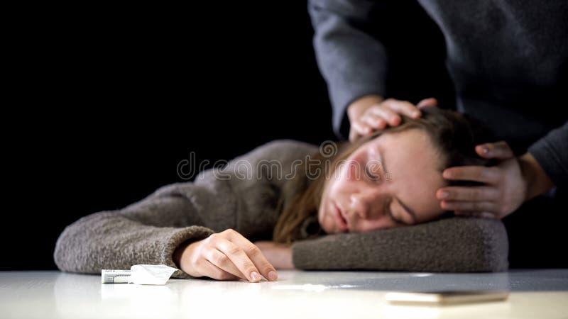 Señora que comprueba a la mujer inconsciente que sufre el envenenamiento narcótico, sobredosis de droga fotografía de archivo libre de regalías