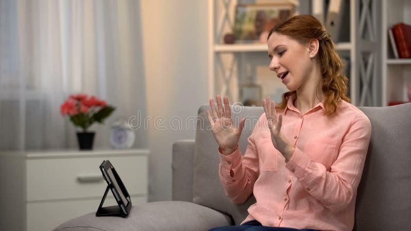Señora que comunica por gestos del asl con el amigo vía la tableta, lengua para sordo fotos de archivo