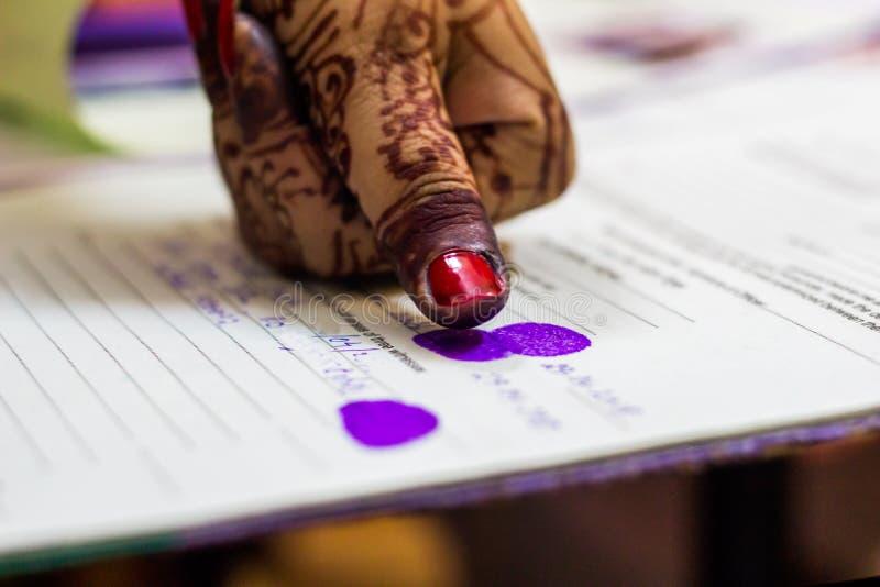 Señora que da la impresión del pulgar en certificado del registro de la boda Matrimonio indio El weddding bengalí imagen de archivo libre de regalías