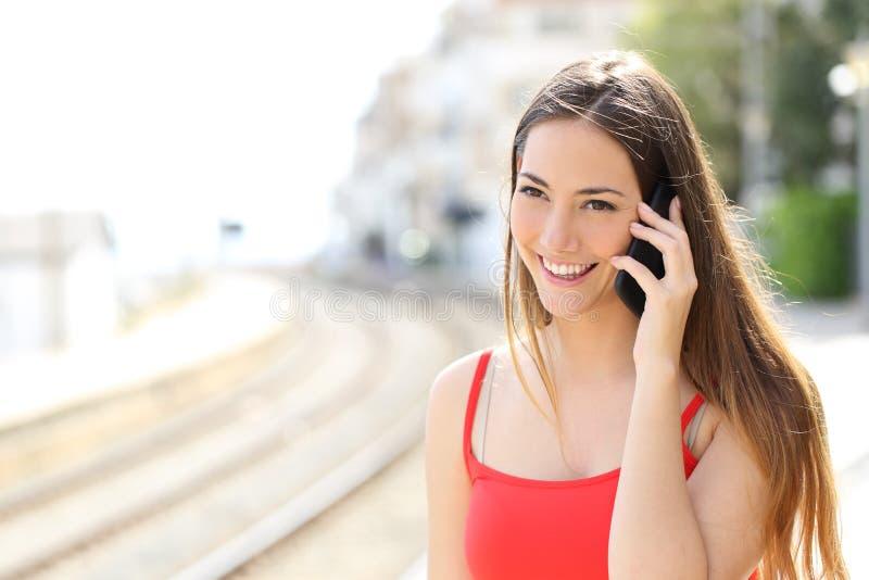 Señora que habla en el teléfono móvil en una estación de tren imágenes de archivo libres de regalías