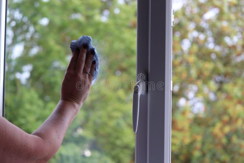 Señora que limpia las ventanas en una casa moderna foto de archivo