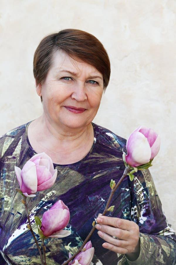 Señora que lleva a cabo una rama de la magnolia fotografía de archivo