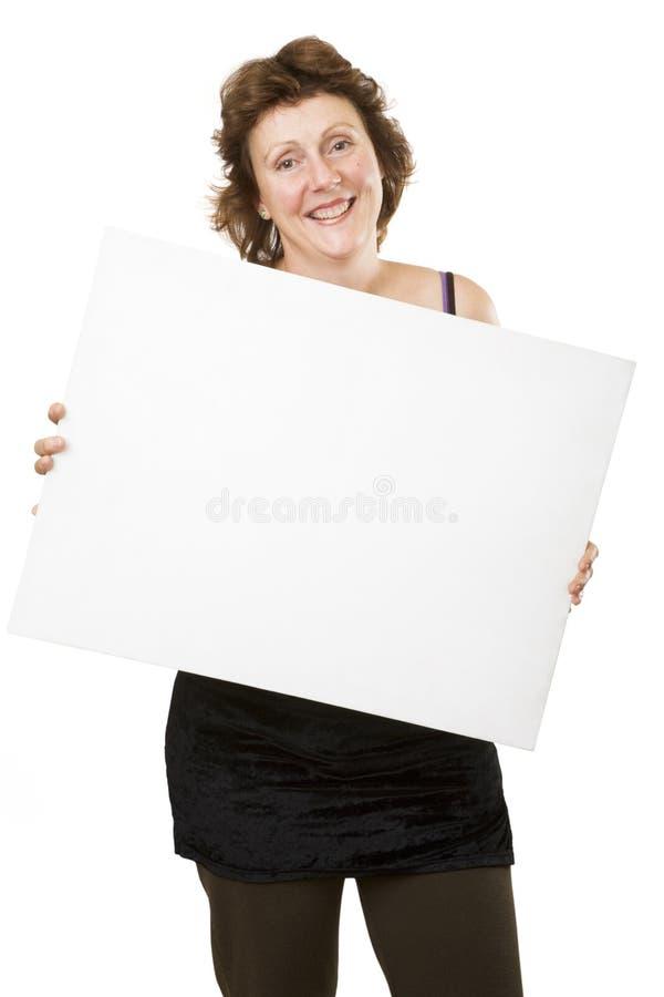 Señora que lleva a cabo a una tarjeta blanca imagen de archivo
