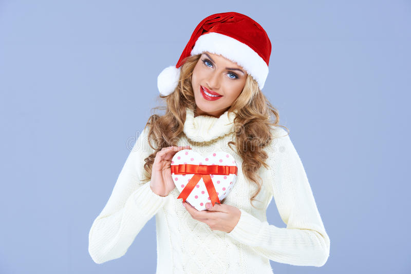 Señora que lleva el sombrero de santa que presenta el regalo imágenes de archivo libres de regalías