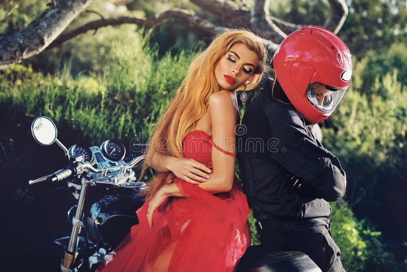 Señora que lleva el vestido rojo que se sienta en la motocicleta con el hombre imagenes de archivo