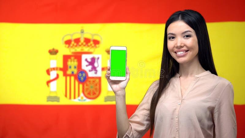 Señora que muestra el teléfono móvil con la pantalla verde, bandera española en el fondo, app del viaje fotografía de archivo