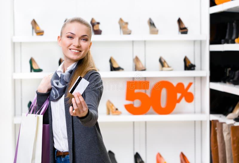 Señora que muestra la tarjeta de crédito en tienda del calzado imagen de archivo