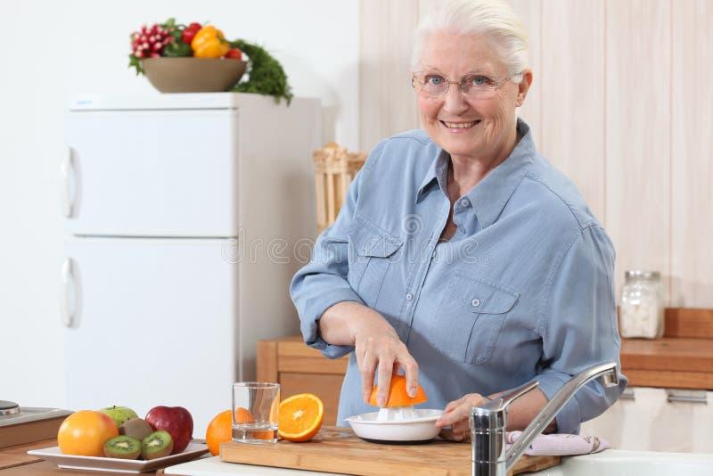 Señora que presiona naranjas. imagen de archivo libre de regalías