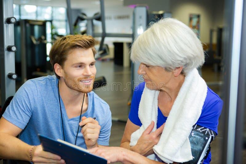 Señora que se resuelve con el instructor masculino joven sonriente amistoso imagenes de archivo