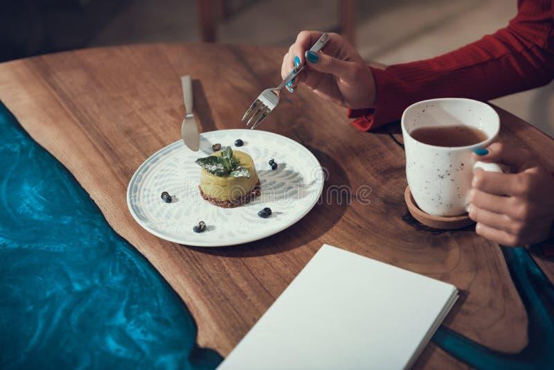 Señora que sostiene la taza de té y que toma la bifurcación mientras que come la torta foto de archivo libre de regalías