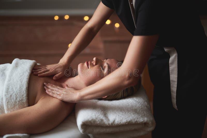 Señora que tiene masaje decollete en salón del balneario foto de archivo