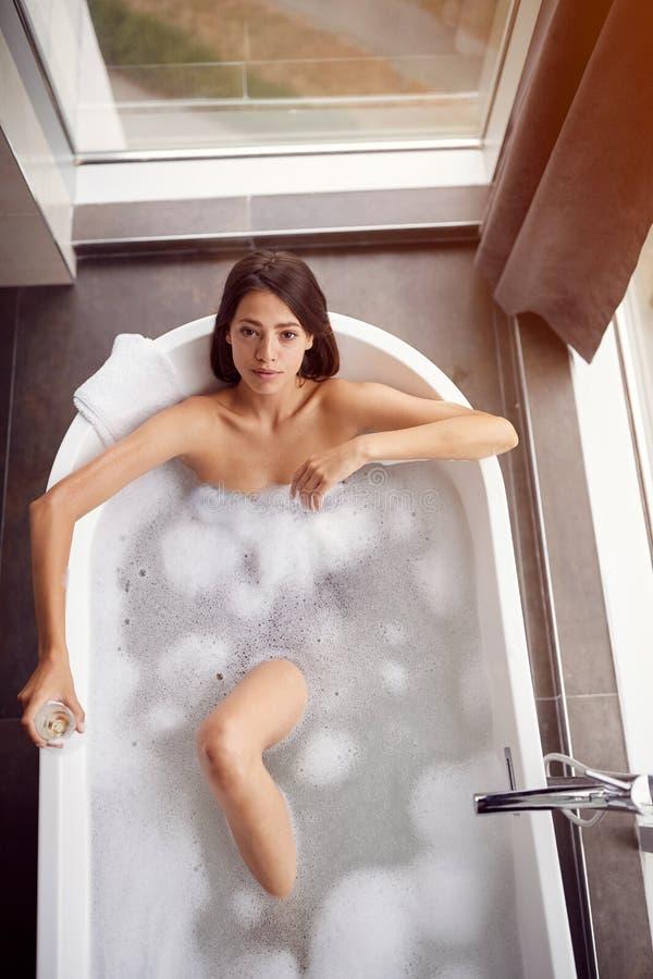 Señora que toma el baño en su opinión superior de la tina hermosa fotos de archivo