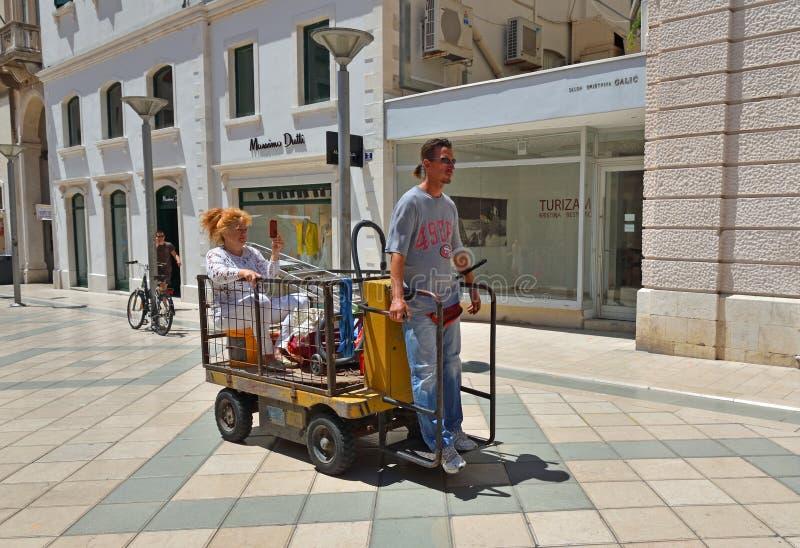 Señora que toma un paseo en una carretilla eléctrica del equipaje, Croacia partido imagen de archivo
