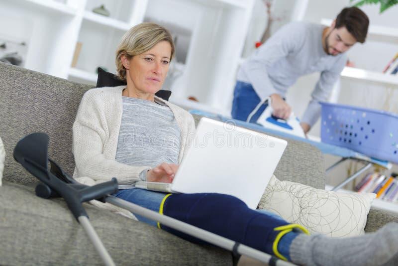 Señora que usa el ordenador portátil mientras que el planchar auxiliar de la ayuda a domicilio fotos de archivo