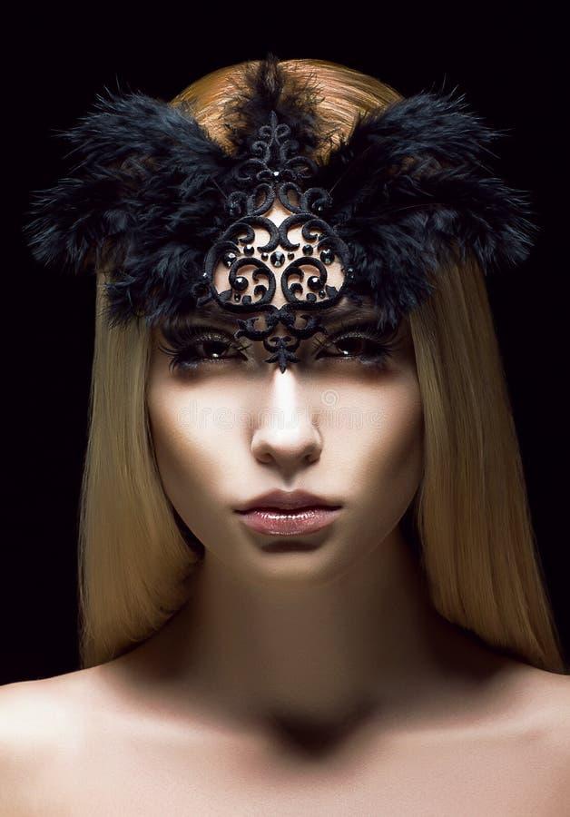 Mujer auténtica hermosa en máscara negra diseñada con las plumas. Cara aristocrática imagenes de archivo